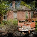 Rusted car outside mortuary, derelict Hellingly Asylu, West Sussex, UK