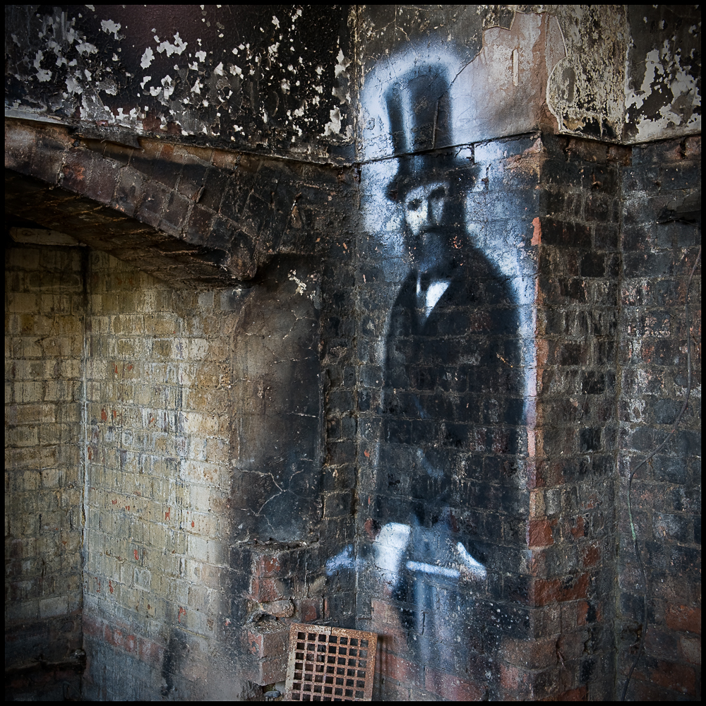 Man in top hat painted on wall of derelict Hellingly Asylum by artist Req, West Sussex